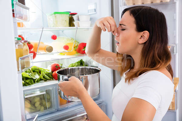 Woman Holding Foul Food Near Refrigerator Stock photo © AndreyPopov