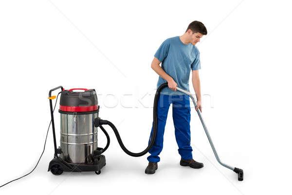 Uomo pulizia piano aspirapolvere giovane bianco Foto d'archivio © AndreyPopov