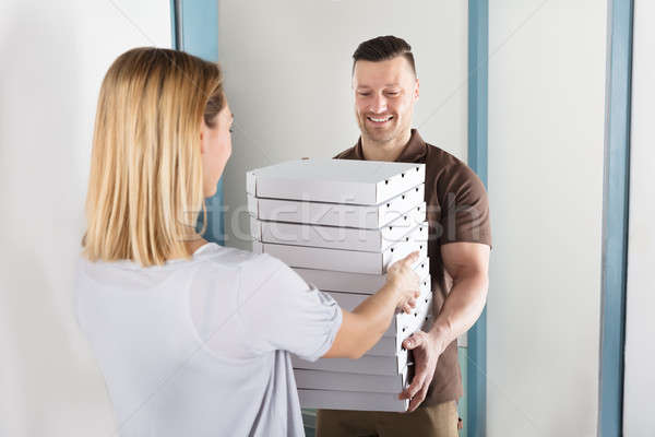 Man Delivering Stack Of Pizza Stock photo © AndreyPopov
