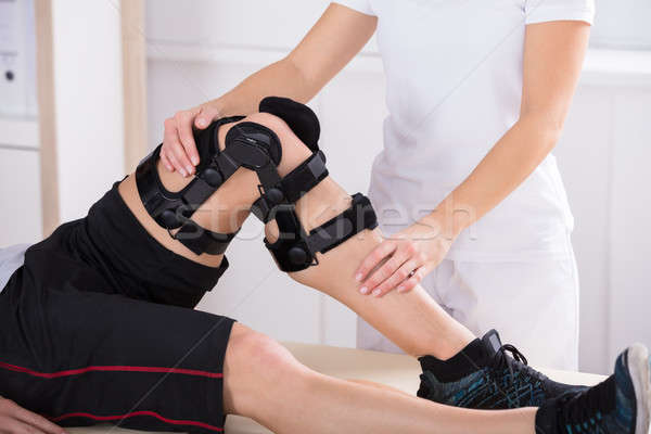 Physiotherapist Giving Leg Exercise Stock photo © AndreyPopov