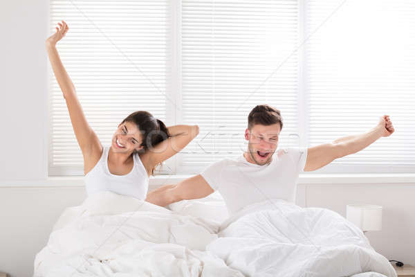 Happy Couple Waking Up On Bed Stock photo © AndreyPopov