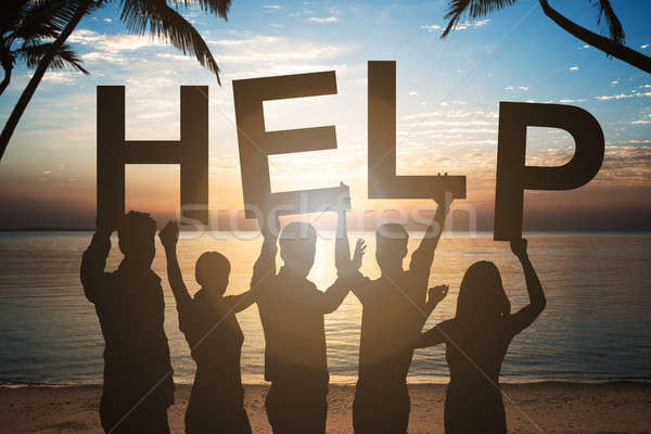Business People Holding Help Text By Sea Against Sky Stock photo © AndreyPopov