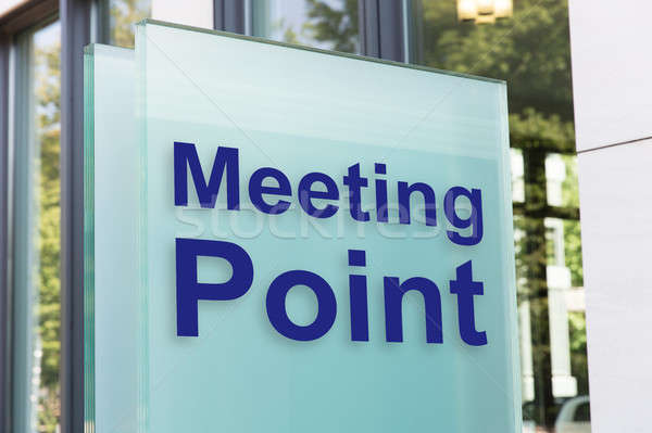 Meeting point on glass board outside building in city Stock photo © AndreyPopov