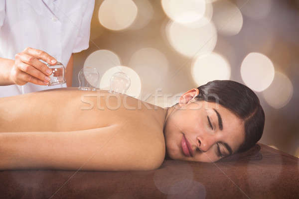 Therapist Placing Transparent Glass Cups On Woman's Back Stock photo © AndreyPopov
