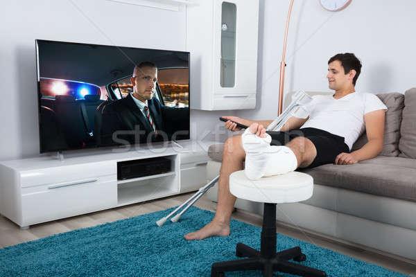 Sebesült férfi tv nézés fiatalember törött láb ül Stock fotó © AndreyPopov