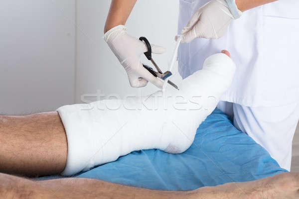 Doctor Tying Bandage On Person's Foot Stock photo © AndreyPopov