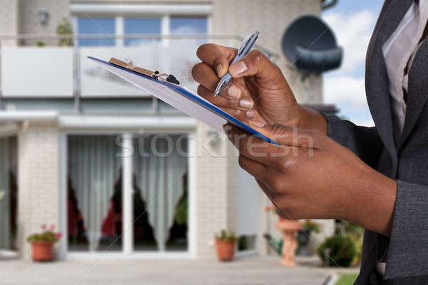 Person Filling Document In Front Of House Stock photo © AndreyPopov