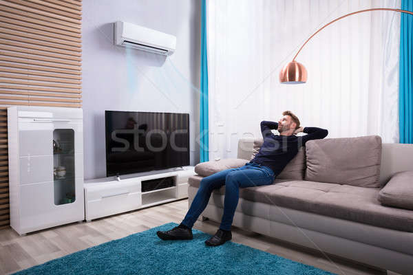 Young Man Relaxing On Sofa Stock photo © AndreyPopov