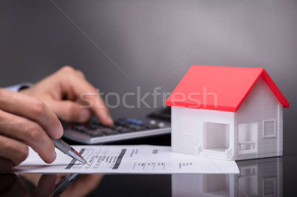 Businessperson Calculating Invoice Besides House Model Stock photo © AndreyPopov