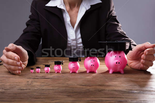 Human Hand Protecting Piggybanks With Graduation Hat Stock photo © AndreyPopov
