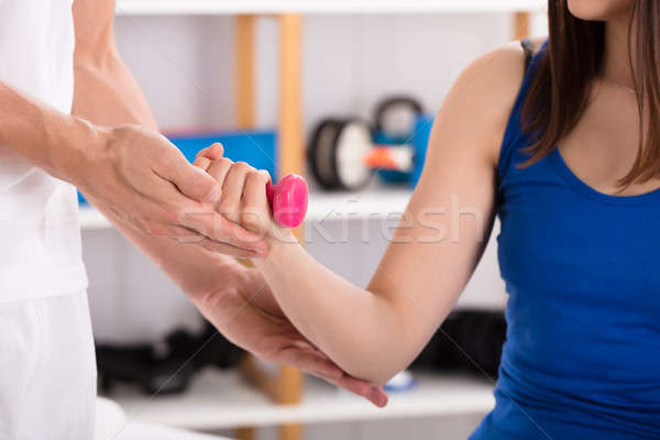 Close-up Of Instructor Assisting Woman While Doing Exercise Stock photo © AndreyPopov