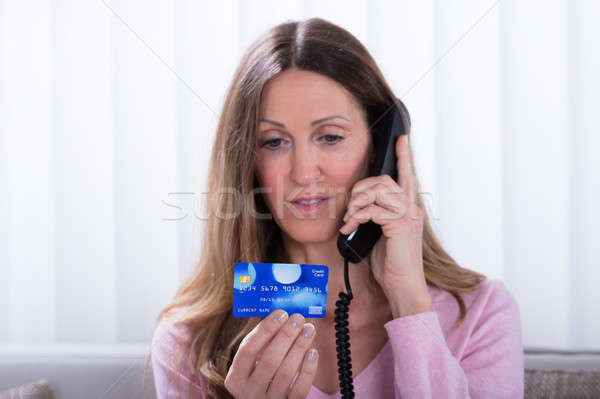Woman Holding Credit Card While Talking On Telephone Stock photo © AndreyPopov