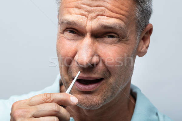 Man In Pain Removing Nose Hair With Tweezers Stock photo © AndreyPopov