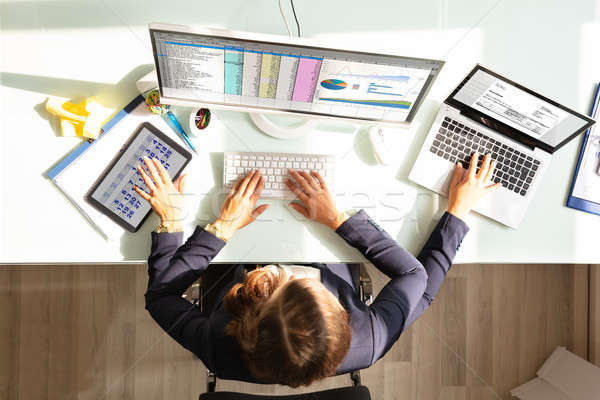 Businesswoman Doing Multitasking Work In Office Stock photo © AndreyPopov