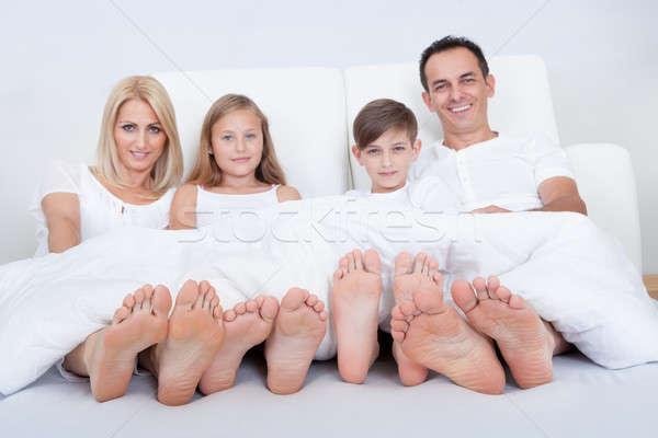 счастливая семья кровать охватывать ног два Сток-фото © AndreyPopov