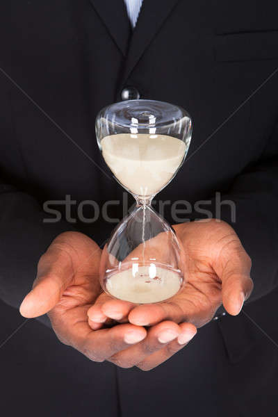 Businessman Holding Hourglass Stock photo © AndreyPopov