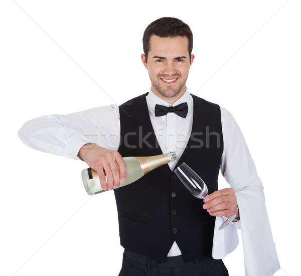 Portrait of butler pouring champagne into glass Stock photo © AndreyPopov
