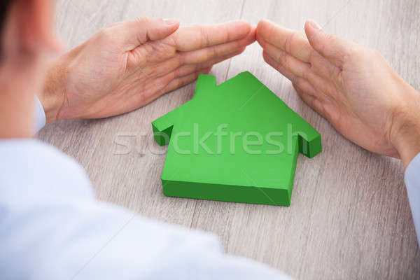 Businessman Forming Hand Frame Around Green House Model Stock photo © AndreyPopov