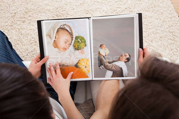 Couple Looking At Photo Album Stock photo © AndreyPopov