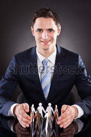 Smiling Businessman Joining Puzzle Pieces At Desk Stock photo © AndreyPopov