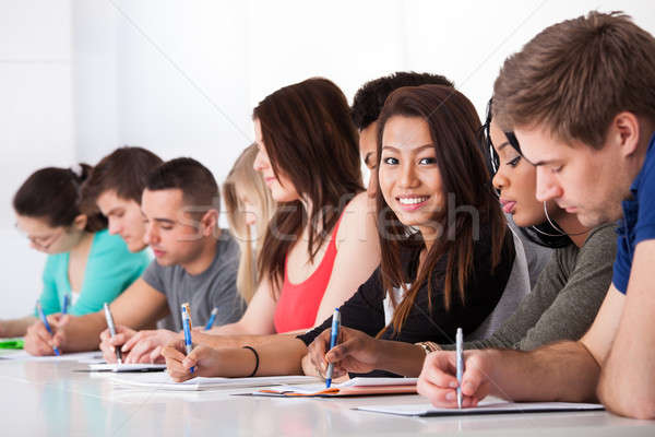 Female Student Sitting With Classmates Writing At Desk Stock photo © AndreyPopov