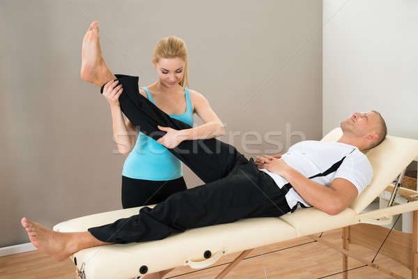 Female Instructor Helping Man For Exercising Stock photo © AndreyPopov