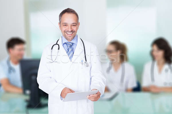 Doctor Holding Digital Tablet Against Team In Meeting Room Stock photo © AndreyPopov
