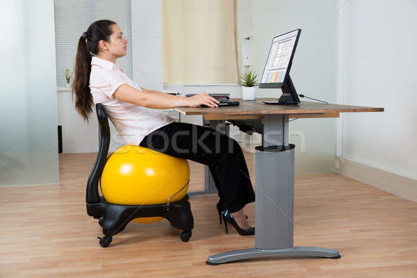 Businesswoman With Fitness Ball And Computer Stock photo © AndreyPopov