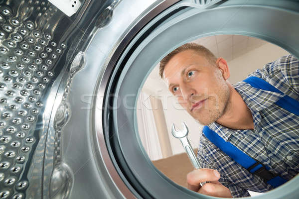 Repairman Looking Inside The Washing Machine Stock photo © AndreyPopov