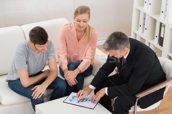 Financial Advisor Showing Graph To Couple Stock photo © AndreyPopov