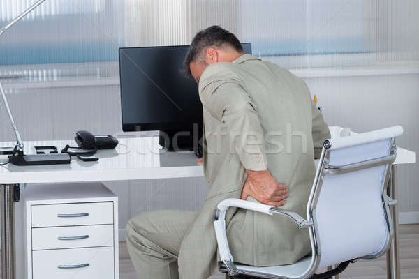 Businessman Suffering From Backache On Chair Stock photo © AndreyPopov