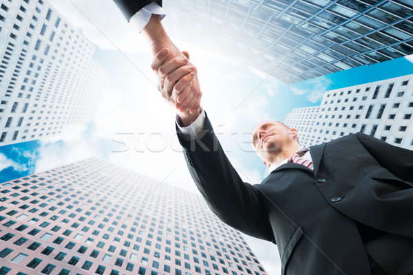 Businessman Shaking Hand With Partner Against Office Buildings Stock photo © AndreyPopov