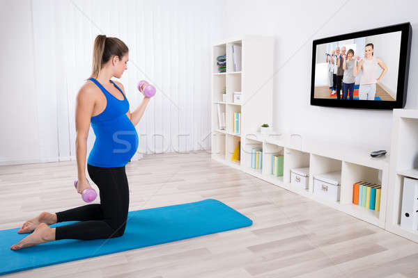 Pregnant Woman Doing Exercise With Dumbbells Stock photo © AndreyPopov