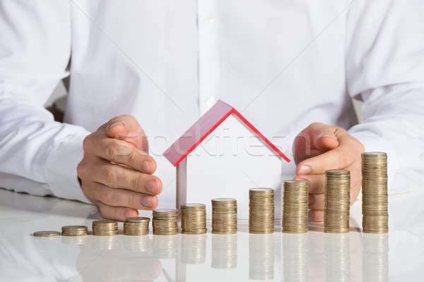 Businessman Protecting House Model With Stacked Coins At Desk Stock photo © AndreyPopov