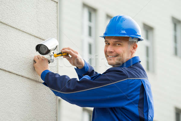 Mature Technician Installing Camera On Wall With Screwdriver Stock photo © AndreyPopov