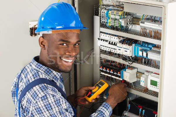 Stock photo: Technician Examining Fusebox With Multimeter Probe