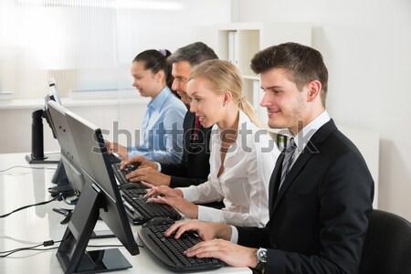 üzletemberek gépel asztali számítógép csoport asztal számítógép Stock fotó © AndreyPopov