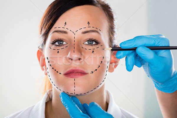 Person's Hand Drawing Correction Line On Woman's Face Stock photo © AndreyPopov