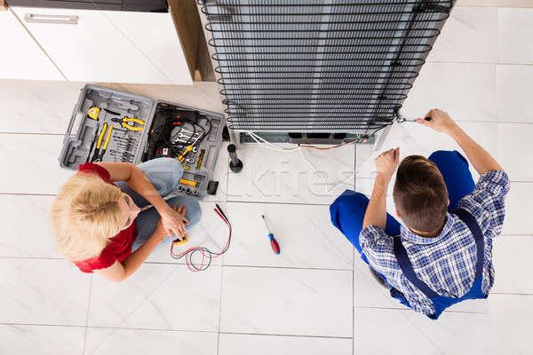 Férfi munkás javít hűtőszekrény konyha szoba Stock fotó © AndreyPopov