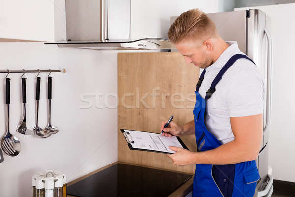 Young Repairman Checking Kitchen Extractor Filter Stock photo © AndreyPopov
