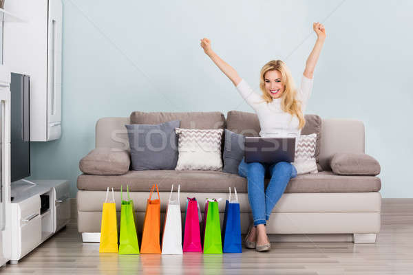 Excited Woman Sitting On Couch With Laptop Stock photo © AndreyPopov