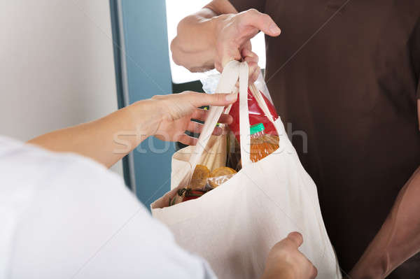 Man Giving Bag Of Grocery To Woman Stock photo © AndreyPopov
