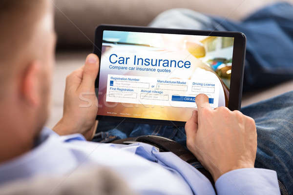 Man Filling Car Insurance Form On Digital Tablet Stock photo © AndreyPopov