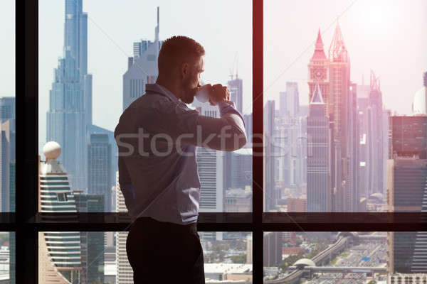 Businessman Drinking Coffee And Looking At City Skyline Stock photo © AndreyPopov