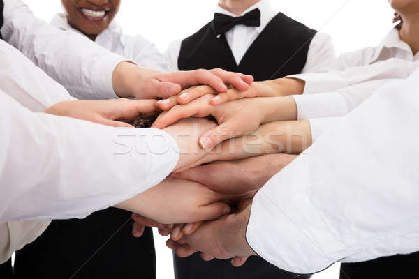 Smiling Young Restaurant Staff Stacking Hands Stock photo © AndreyPopov