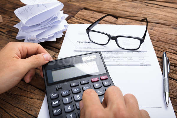 Businessman Calculating Invoice At Table Stock photo © AndreyPopov