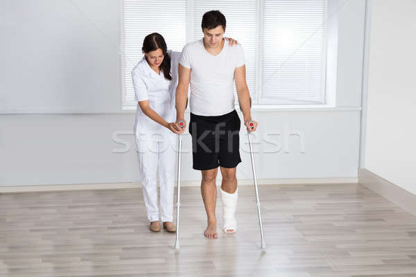 Physiotherapist Assisting Injured Patient To Walk With Crutches Stock photo © AndreyPopov