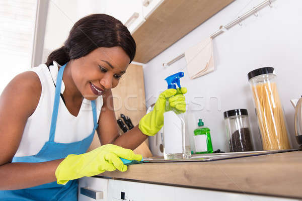 Woman Cleaning Kitchen Sink With Yellow Cloth And Spray Bottle Stock photo © AndreyPopov