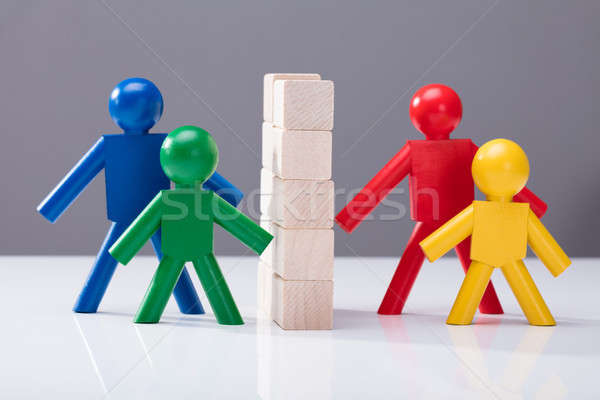 Human Figures Separated By Stacked Wooden Blocks On White Desk Stock photo © AndreyPopov