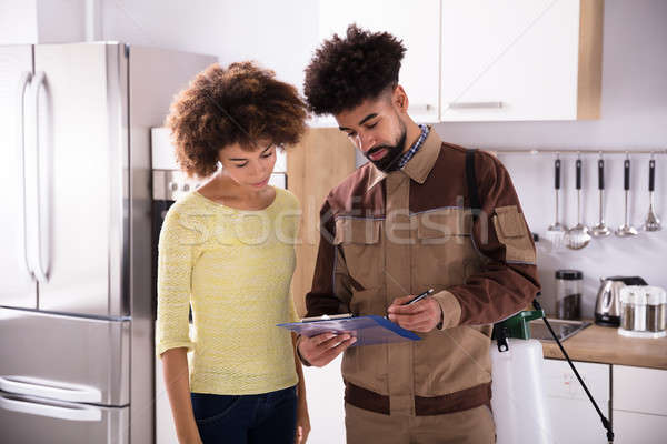 Pest Control Worker Showing Invoice To Woman Stock photo © AndreyPopov